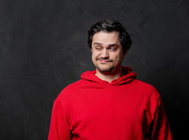暗い壁に赤いスウェットシャツを着た白い愚か者