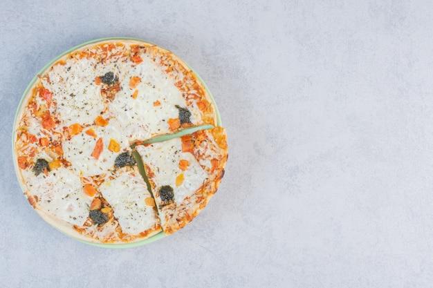 Pizza ai quattro formaggi bianca con parmigiano fuso su fondo grigio.