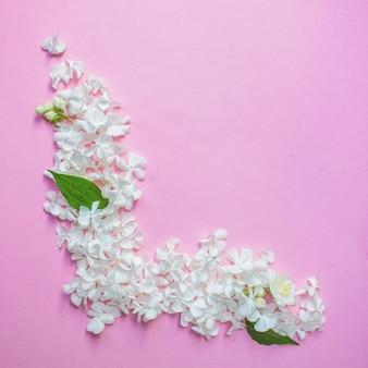 흰색 프레임 공백, 스파용 꽃잎 또는 분홍색 배경 상단 보기에 있는 결혼식 모형. 아름다운 꽃