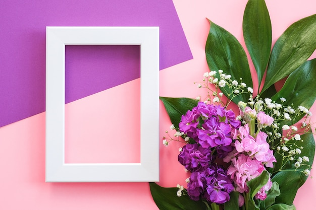 White frame and bouquet flowers on pink purple