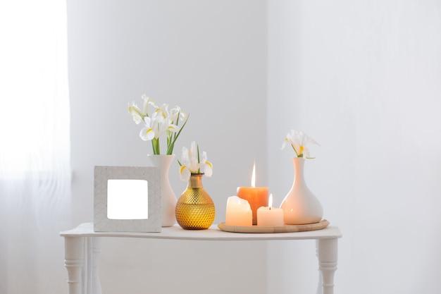 Белая рамка, зажженные свечи и цветы на полке на белом фоне