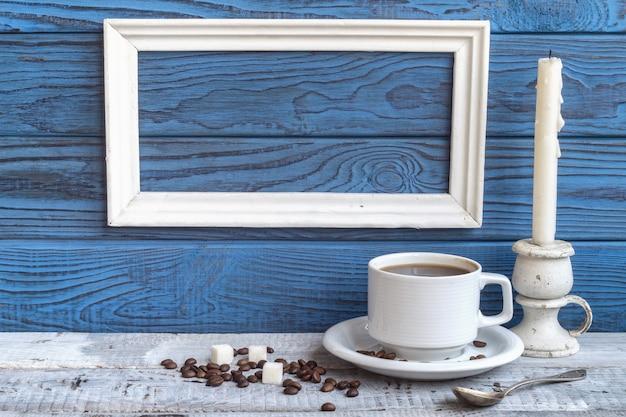 블루 보드의 배경에 흰색 프레임, 커피 컵 및 캔들