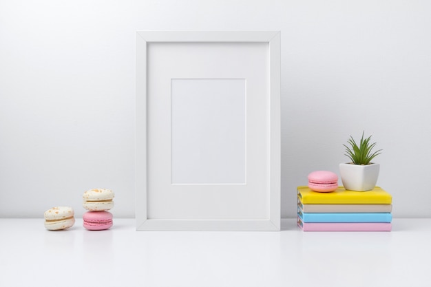 White frame, colorful notepads, plant and macaroons on book shelf or desk