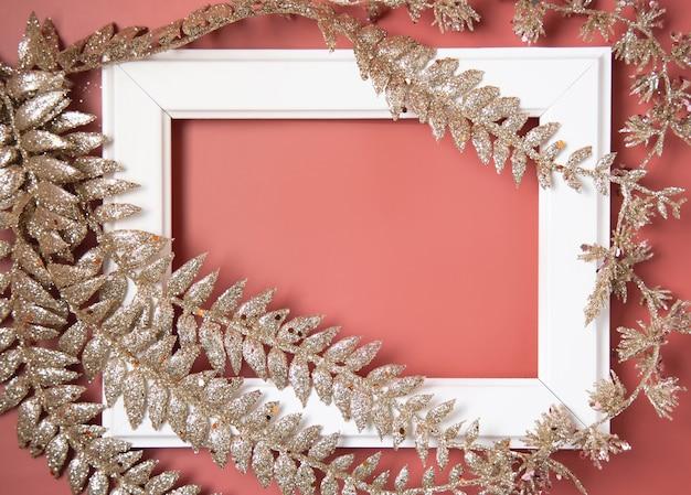 ピンクの背景の上面図にクリスマスの黄金の葉で覆われ、飾られた白いフレーム