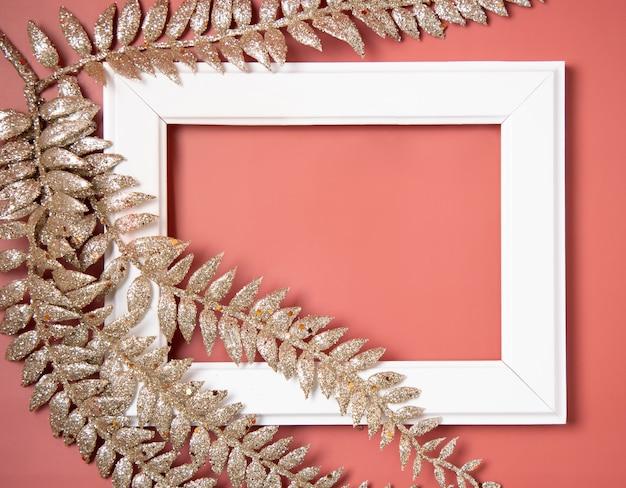 ピンクのクリスマスの黄金の葉で覆われた白いフレーム