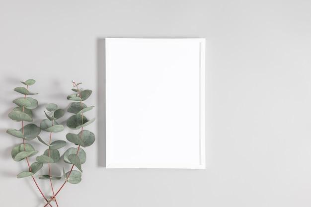White frame and eucalyptus on gray table