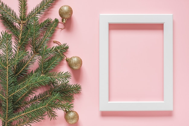 White frame and green spruce branch with gold christmas balls on pink