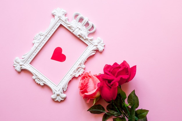 A white frame and hearts over pink wall and a bouquet of red roses