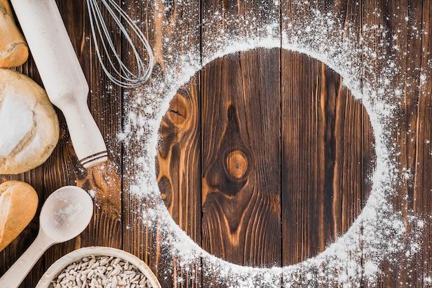 밀가루와 나무 배경에 신선한 빵으로 만든 화이트 프레임