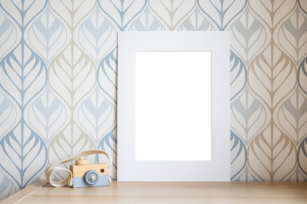 White frame mock up for photo, print art, text or lettering, with kids room decorations and toys. blank frame on wooden table side view