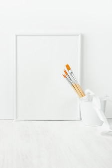 White frame mock up with paint brushes tied with silk ribbon in bucket