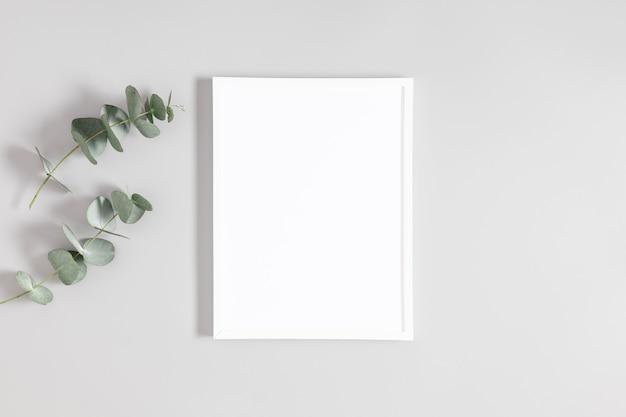 White frame mockup and eucalyptus on gray background