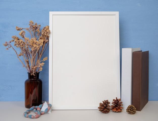 Макет белой рамки для дизайна или текста, книги, сушеный цветок в стеклянной банке, сосновые шишки и старинный камень, сидящий на деревянном столе на синем фоне стены