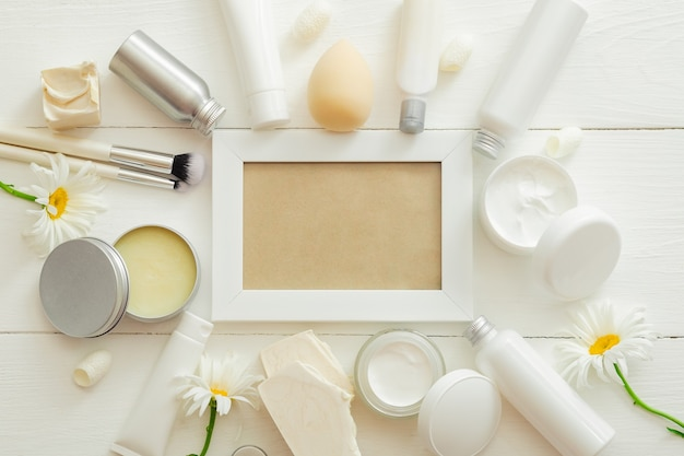 White frame set cosmetic products in white packaging on wooden background with flowers cosmetic bag beauty skin care hair treatment cosmetic moisturizer cream body butter soap shampoo flat lay