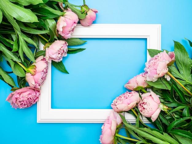 파란색 배경에 아름다운 분홍색 모란으로 둘러싸인 흰색 프레임