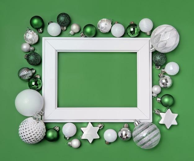 緑の背景のモックアップに緑、銀、白のクリスマスの装飾に囲まれた白いフレーム
