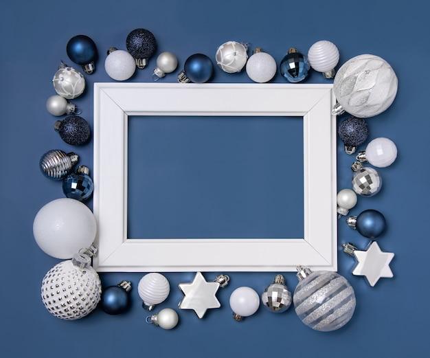 青い背景のモックアップに青、銀、白のクリスマスの装飾で囲まれた白いフレーム