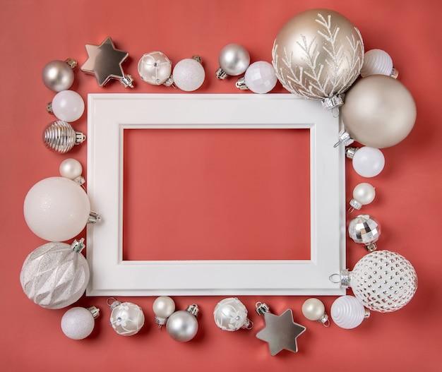 Белая рамка в окружении серебряных и белых елочных игрушек на розовом фоне макета