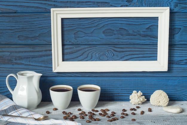흰색 프레임, 두 개의 커피 컵 및 파란색 보드 배경에 있는 주전자