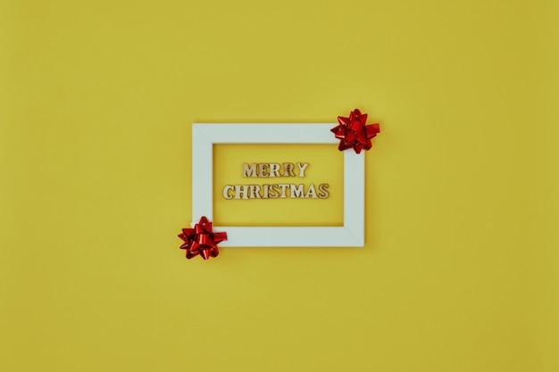 Белая рамка с елочными украшениями и надписью merry christmas на желтом фоне