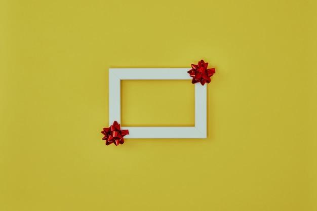 Белая рамка с елочными украшениями на желтом фоне