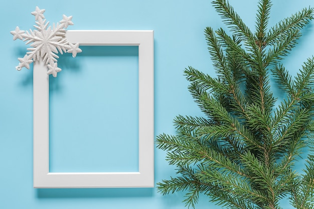White frame with decoration snowflake and green spruce branch on blue background.