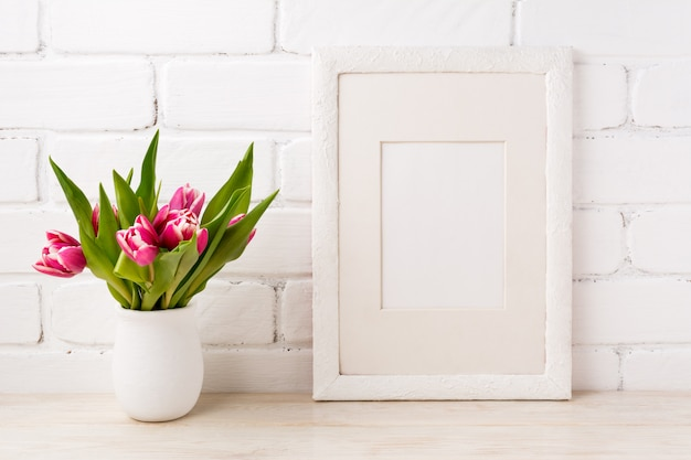 White frame with magenta pink tulip in the flower pot