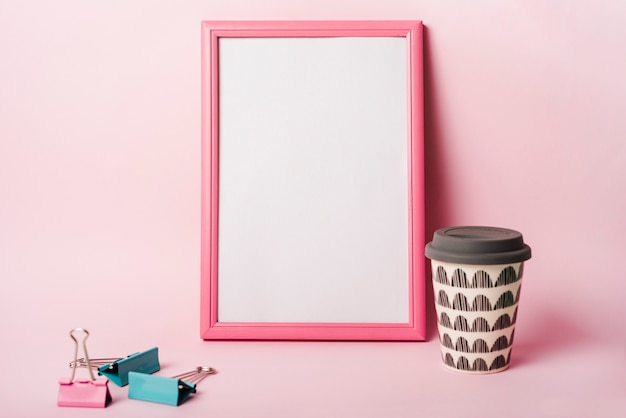White frame with pink border; paper clips and coffee disposable cup against pink background