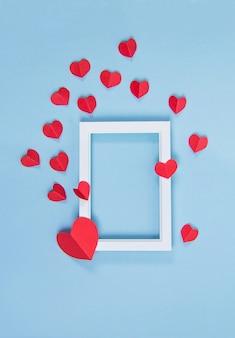 青い背景に赤いハートの白いフレーム、コピースペース、バレンタインデー、愛、招待状