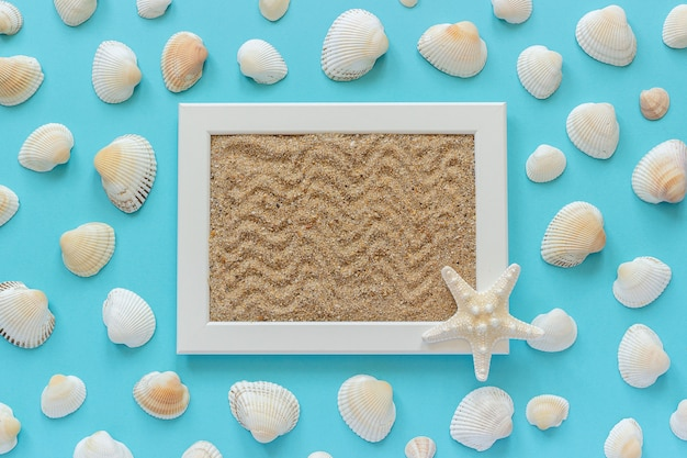 White frame with sea sand and starfish, seashells on blue background