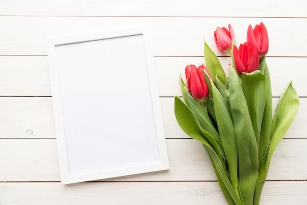 白い木製の背景の上に春のチューリップの上面図と白いフレーム。デザインをモックアップします。