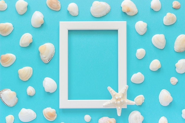 White frame with starfish on blue background and seashells