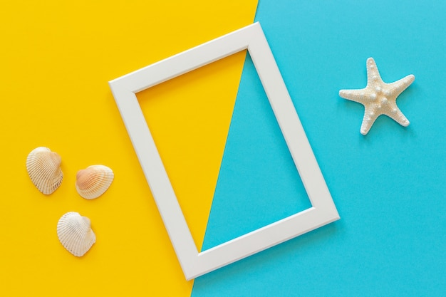 White frame with starfish on blue, yellow background and seashells.