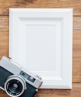 White frame on wooden background with old camera