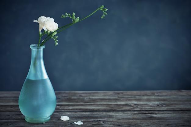 Белая фрезия в стеклянной вазе на темном