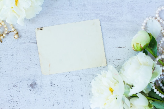 White fresh blooming peony flowers vintage flat lay scene with empty paper note