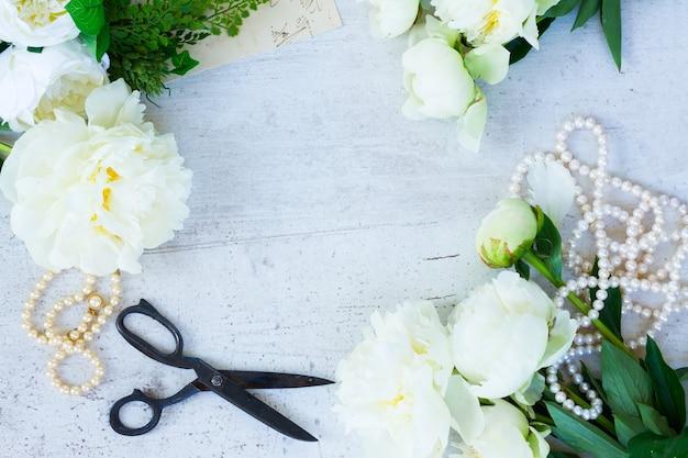 Белые свежие цветущие цветы пиона с украшениями из жемчуга на белой деревянной раме рабочего стола