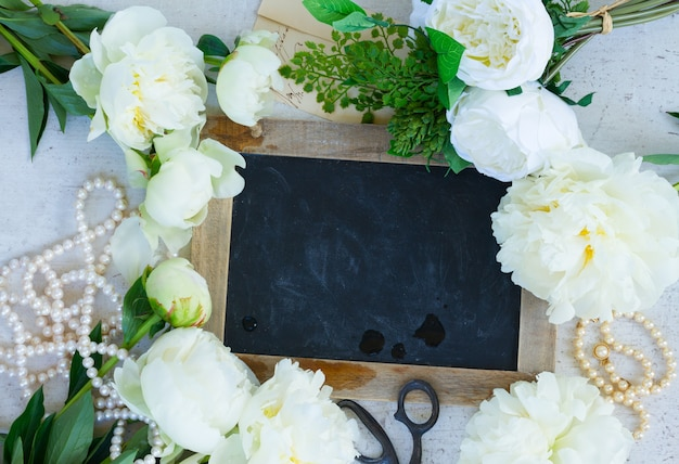 Белые свежие цветущие цветы пиона с украшениями из жемчуга на белой деревянной раме стола