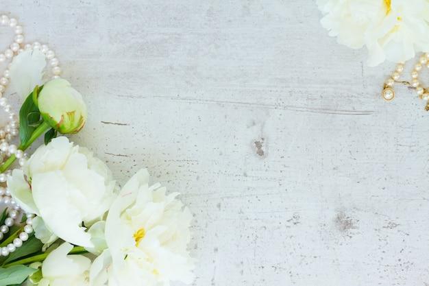 Белые свежие пионы и бутоны с жемчужными украшениями на старом белом деревянном столе