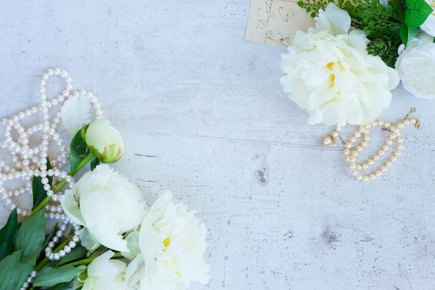 Белые свежие цветы пиона и бутоны с жемчужными украшениями на старом белом деревянном столе