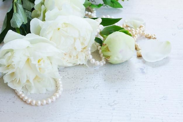 Букет белых свежих пионов с жемчужными украшениями на белом деревянном столе