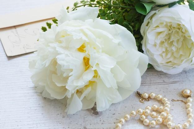 Букет из белых свежих пионов с жемчужными украшениями на белом деревянном столе