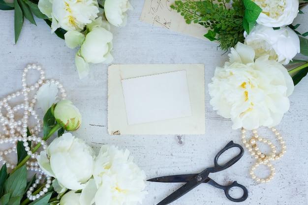 White fresh peony flowers vintage flat lay wedding frame on empty paper note