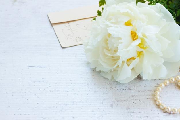 Белые свежие цветы пиона с жемчужными украшениями и буквой на белом деревянном столе