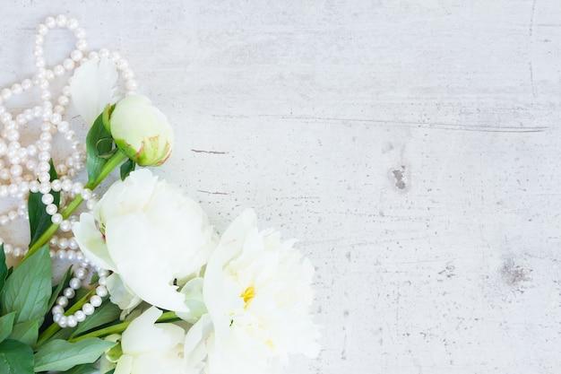 Белые свежие цветы пиона с украшениями из жемчуга на старом белом деревянном столе