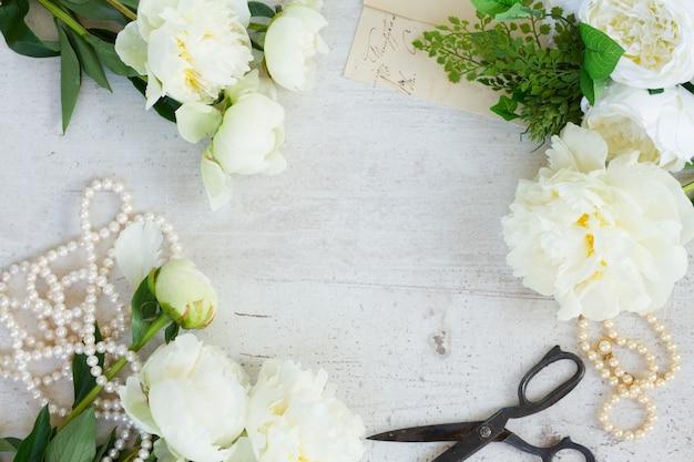 Белые свежие цветы пиона с украшениями из жемчуга на белой деревянной раме рабочего стола