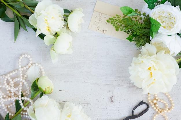 Белые свежие цветы пиона с украшениями из жемчуга на белой деревянной раме стола