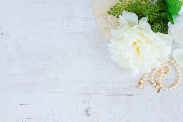 Белые свежие цветы пиона с украшениями из жемчуга на белом деревянном столе