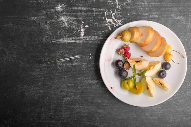 Piatto di frutta bianca isolato su sfondo nero a destra