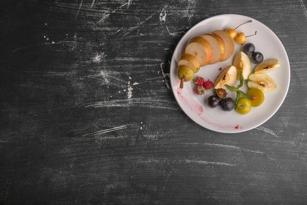 黒の背景に分離された白いフルーツの盛り合わせ